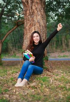 公園で育った腕の本を持っている陽気な女性