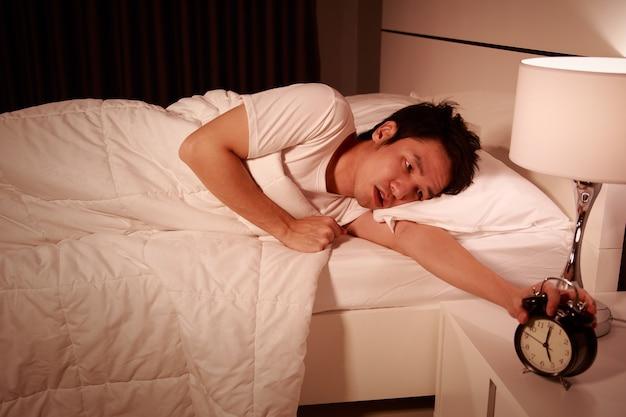 朝の寝室の目覚まし時計で目が覚めた不幸な男