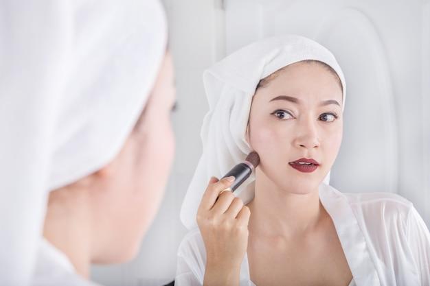 ミラーで見て、ブラシで化粧を塗る女性
