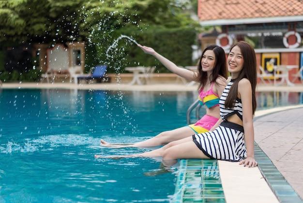 Две молодые женщины друзья брызг воды в бассейн