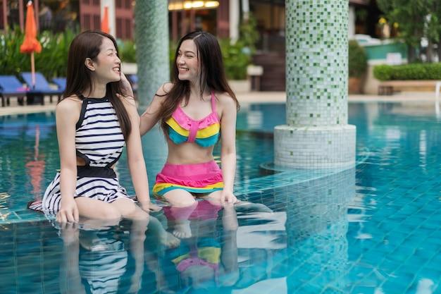 Две молодые женщины-друзья пользуются в бассейне
