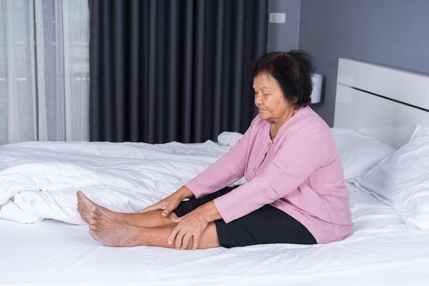 ベッドで脚の痛みを持つシニアの女性