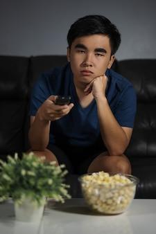 夜はリビングルームのテレビを見てソファに座っている退屈な男