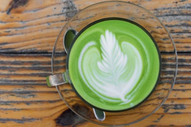 テーブル上のホットミルクの緑茶のカップ
