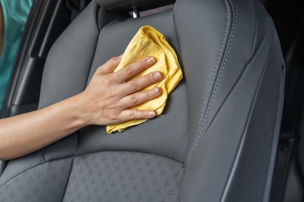 マイクロファイバー布で革のシートをクリーニングする手