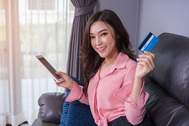 リビングルームのクレジットカードでオンラインショッピングでデジタルタブレットを使用している幸せな女性