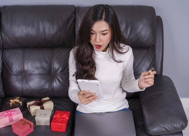 Удивленная женщина покупки онлайн для подарка с ноутбуком в гостиной