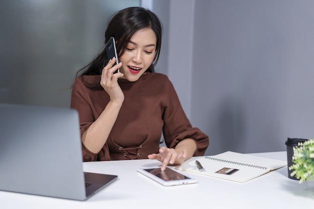 スマートフォンとデジタルタブレットを使ってオンラインショッピングをする女性