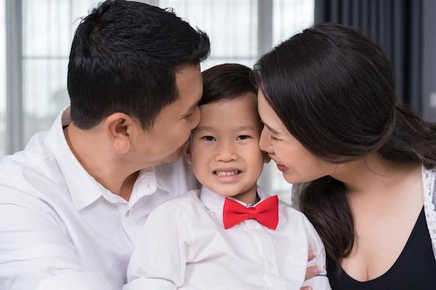 幸せな家族の概念、妊娠中の母親と父親の子供男の子にキス