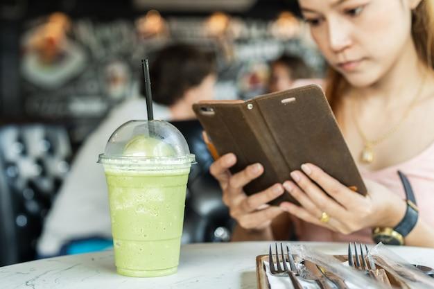 緑茶のフラッペに写真を撮るモバイルのスマートフォンを保持している女性