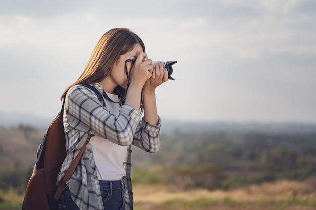 観光女性が彼女のカメラで自然に写真を撮る