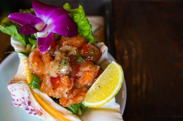 レストランの料理にサーモン刺身のピリ辛サラダ