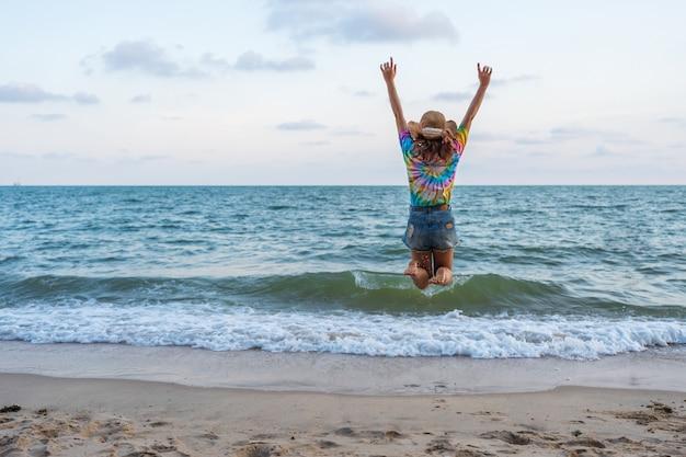 Женщина наслаждается и прыгает на морской пляж