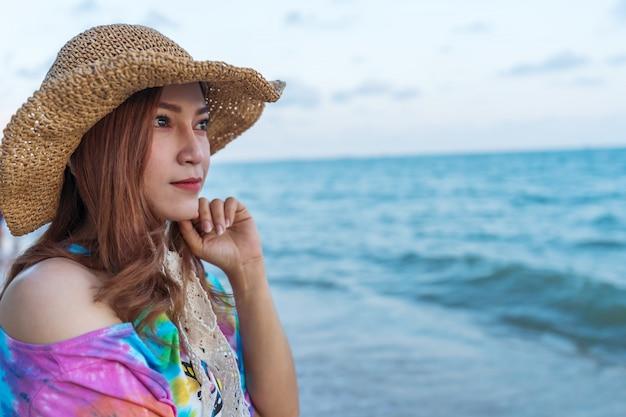海のビーチの上に帽子立っている女性