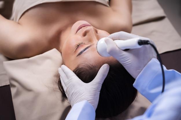 超音波顔の美容トリートメントスキンケアを受ける女性