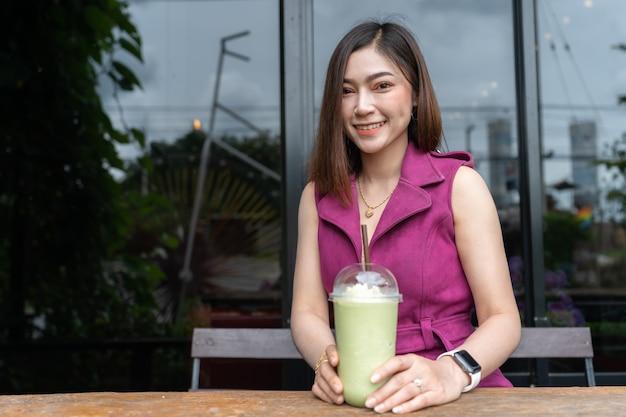 Женщина пьет зеленый чай фраппе в кафе