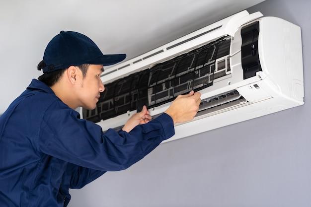 清掃のためのエアコンのエアフィルターを取り外す技術者サービス