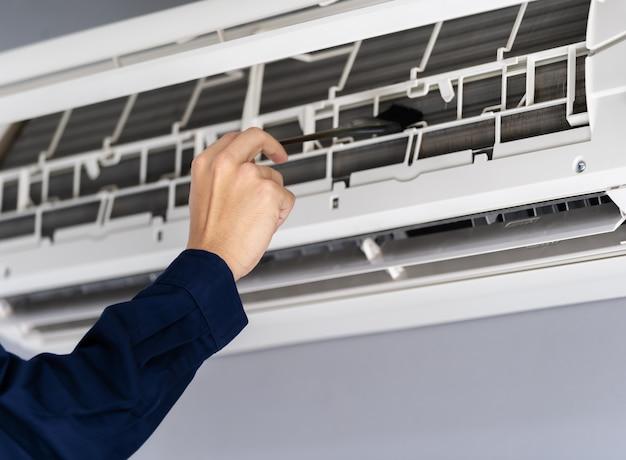 エアコンの掃除にブラシを使用して技術者のサービスをクローズアップ