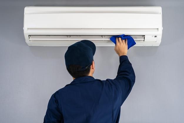 布でエアコンを掃除する技術者サービス