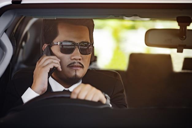 Деловой человек разговаривает по мобильному телефону и ведет машину