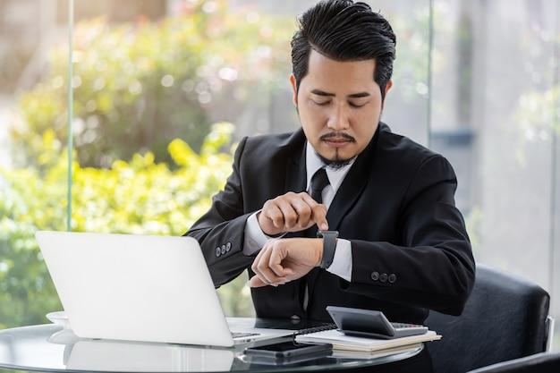 Деловой человек, проверка времени на смарт-часы при использовании ноутбука