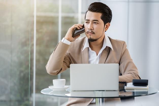 Деловой человек разговаривает по мобильному телефону и использует ноутбук