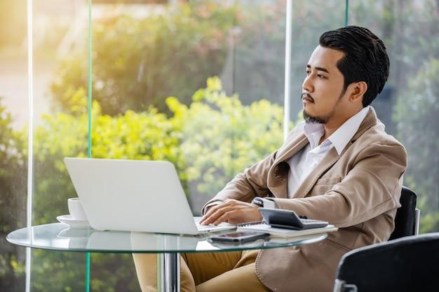 Деловой человек думает и работает с ноутбуком