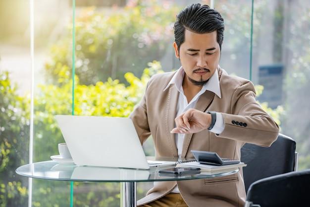 ビジネスの男性のラップトップを使用しながらスマートな時計で時間をチェック