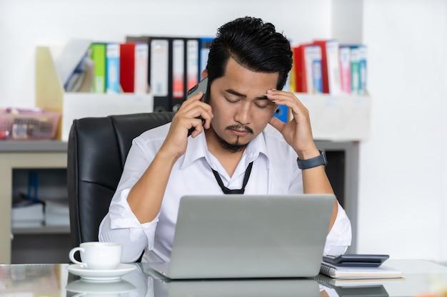意気消沈したビジネスの男性はスマートフォンで話しています。