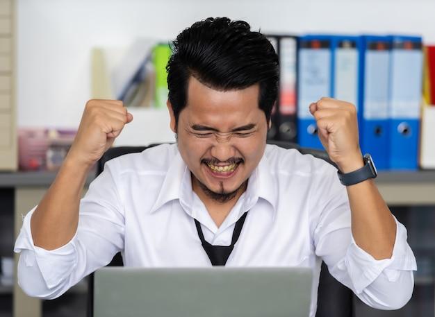 ラップトップコンピューターを使用して幸せな成功するビジネス人