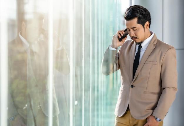 意気消沈したビジネスの男性はオフィスでスマートフォンで話しています。