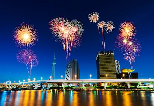 夜、日本の東京の街並みの上の花火