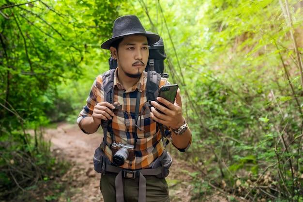 Человек путешественник с рюкзаком, используя смартфон в лесу