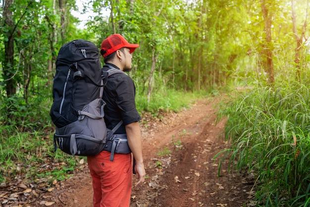 バックパックと森の地図を持つ男旅行者