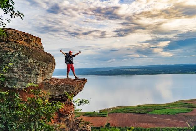 陽気なハイカージェスチャーは、岩山の頂上で、崖の端に腕を上げた