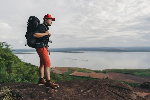 Человек путешественник с рюкзаком, стоя на краю обрыва, на вершине скалы горы