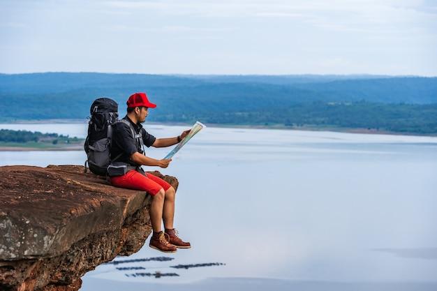 岩山の上に、崖の端にある地図を見てバックパックを持つ男旅行者