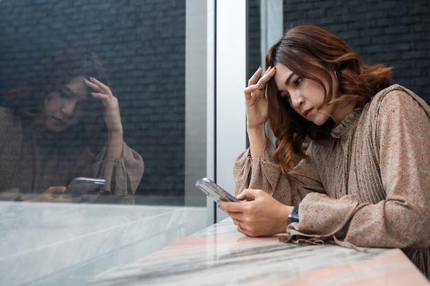 Депрессии женщина смотрит на свой смартфон и с головной болью, грустно, беспокоиться о проблеме