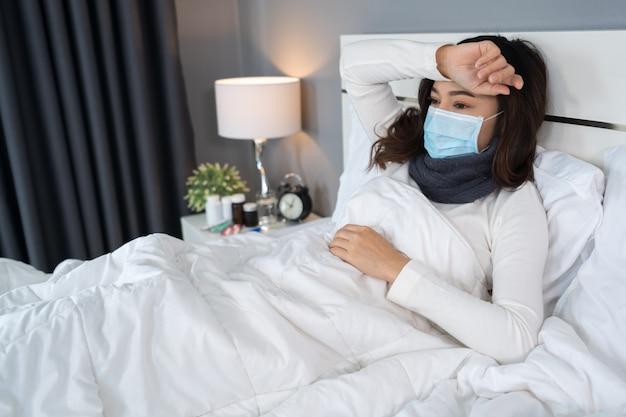 医療マスクの病気の女性は頭痛であり、ウイルス病とベッドでの発熱、コロナウイルスのパンデミックに苦しんでいます。