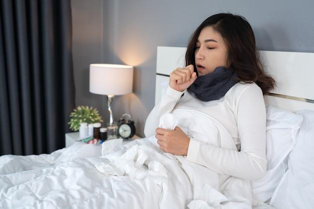 病気の女性が寒さとベッドで咳
