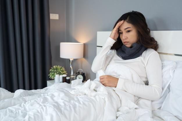 病気の女性はベッドで頭痛です