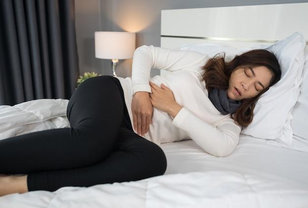 ベッドで胃の痛みを持つ女性