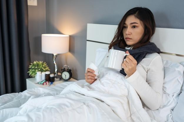 ベッドの上のお湯のカップを飲んで病気の女性