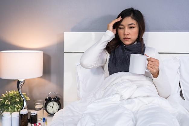 病気の女性の頭痛とベッドの上のお湯のカップを飲む
