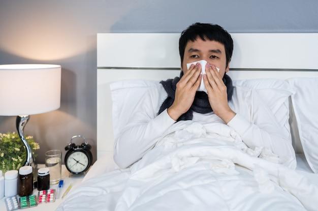 風邪をひいてベッドでくしゃみをする病気の女性