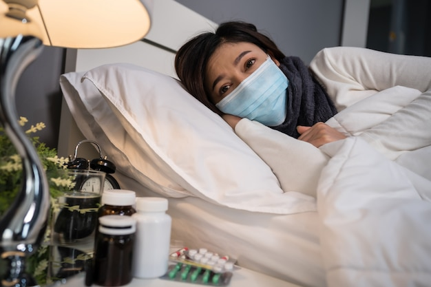 ウイルス性疾患とベッドでの発熱、コロナウイルスのパンデミックの概念に苦しむ医療用マスクの病気の女性。