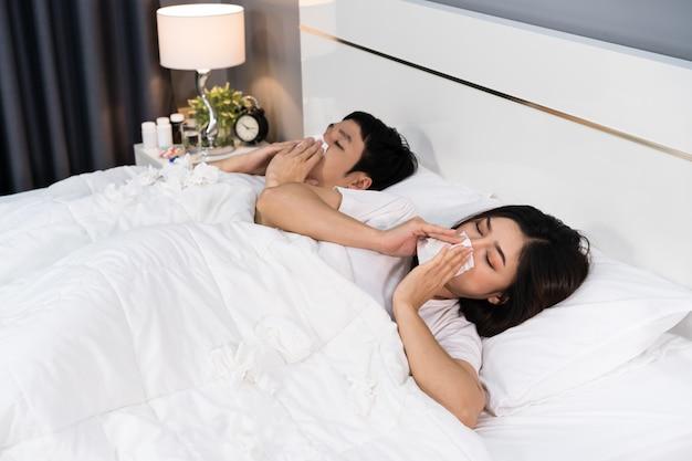 くしゃみをして病気のカップルがベッドでウイルス病と発熱に苦しんでいる