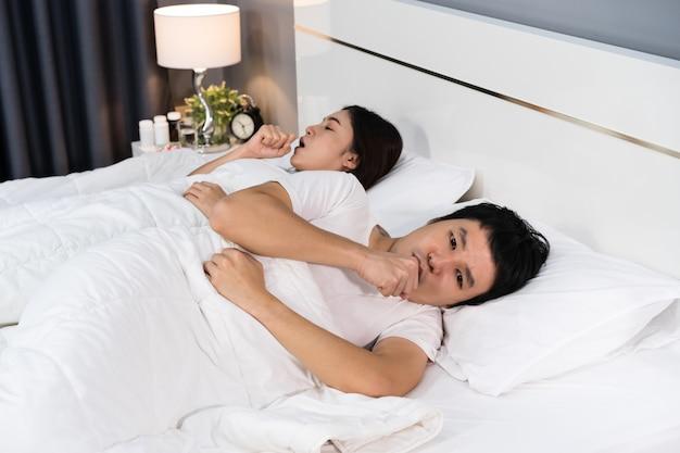 病気のカップルが咳をしてベッドでウイルス病や発熱に苦しんでいる