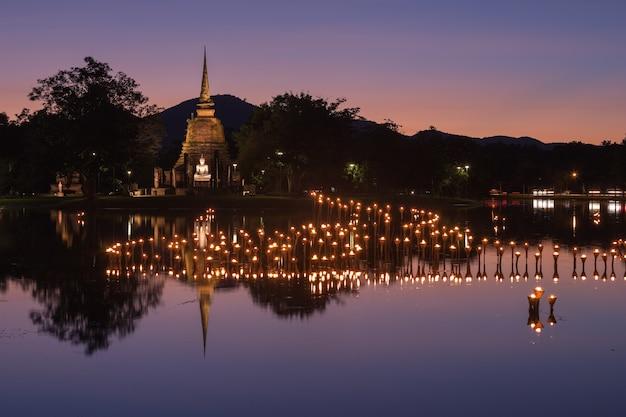 Свет в статуи будды в фестивале лой кратонг, исторический парк сукхотай, таиланд