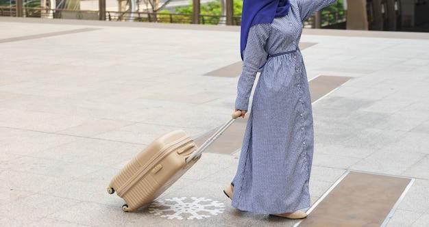 スーツケース付きイスラム教徒旅行者